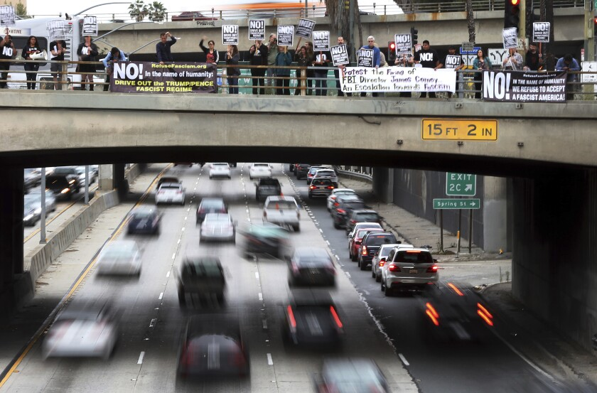 Protesters from the Refuse Fascism group on a bridge over the busy 101 Freeway