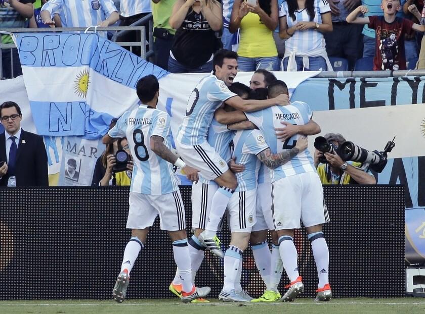 Los jugadores de Argentina abrazan a su compañero Gonzalo Higuaín, escondido atrás, tras anotar un gol contra Venezuela en los cuartos de final de la Copa América Centenario el sábado, 18 de junio de 2016, en Foxborough, Massachusetts. (AP Photo/Elise Amendola)