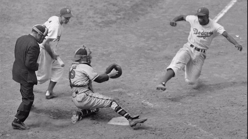 The Dodgers' Jackie Robinson steals home as Boston Braves' catcher Bill Salkeld is thrown off-balanc