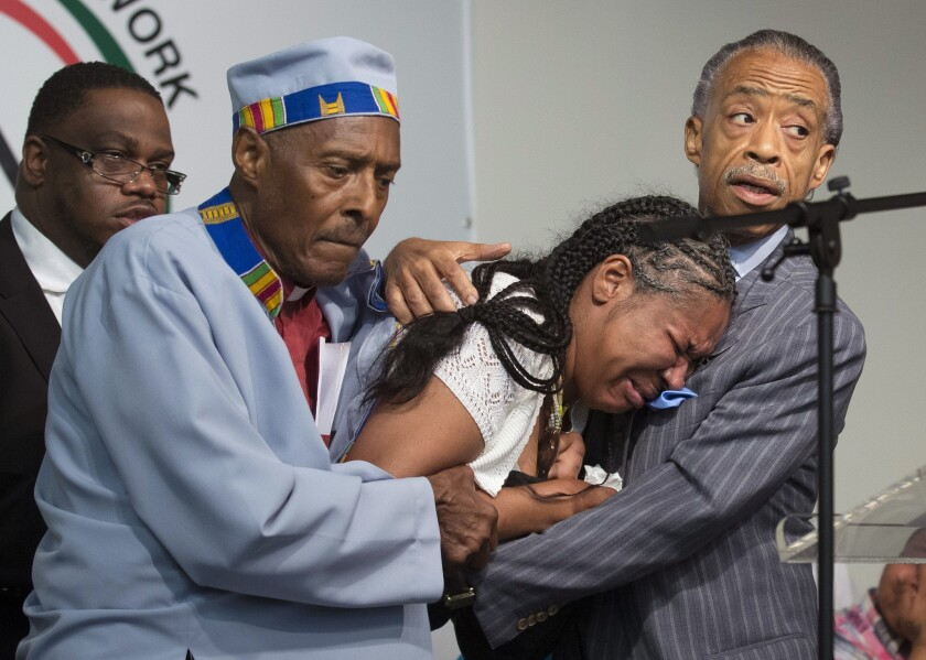 Esaw Garner, wife of Eric Garner, breaks down in the arms of the Revs. Herbert Daughtry, left, and Al Sharpton during a rally over Garner's death in Staten Island, N.Y.