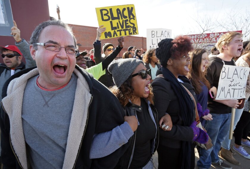 """Protesters Daniel Conford, from left, Tracy Parks, Ashley Carter, Judy Lucas and Luke Davis shout """"Black lives matter"""" as theyfacepolice in Ferguson, Mo., last year."""
