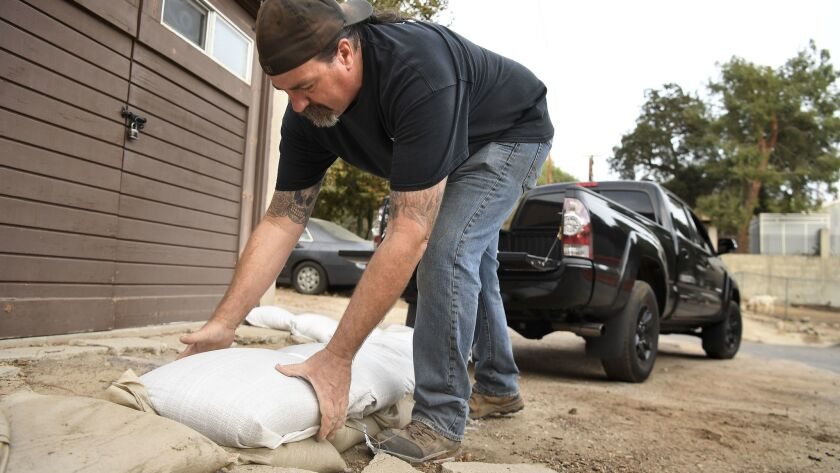Mark Jefferson puts sand bags in front of his house in Kagel Canyon before a storm hits the the Creek fire burn area.