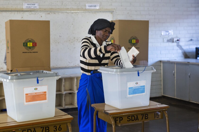 A Zimbabwean woman casts her vote for the presidential elections at the Fitchela primary school in Kwekwe, Zimbabwe, Monday, July 30, 2018.