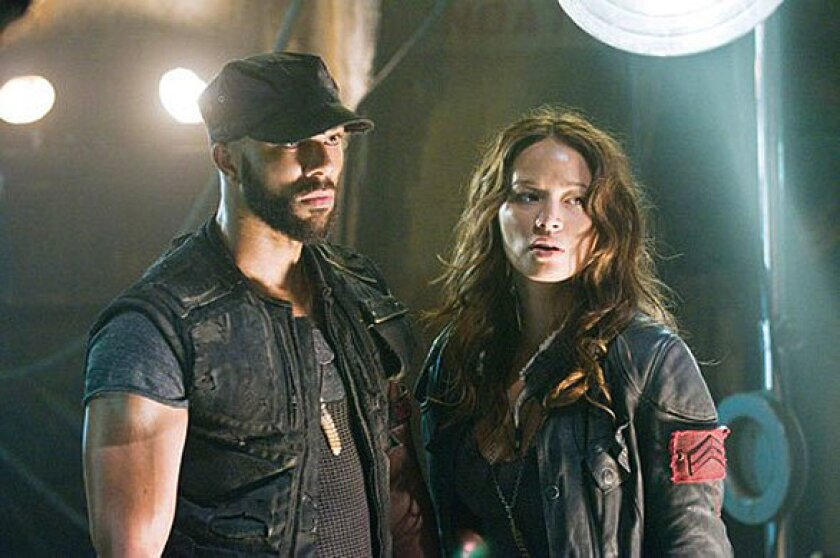 """Rapper Common co-starred in the 2009 movie,  """"Terminator Salvation."""" He is shown here in a scene with with actress Moon Bloodgood."""