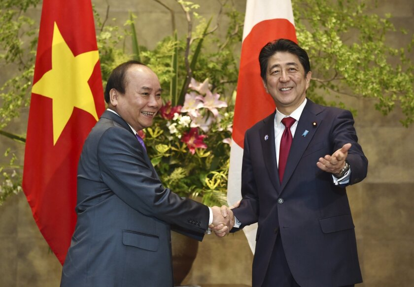 Japanese Prime Minister Shinzo Abe, right, poses with his Vietnamese counterpart Nguyen Xuan Phuc prior to their meeting at Abe's official residence in Tokyo Saturday, May 28, 2016. The bilateral meeting followed a gathering with G-7 leaders after their annual summit in Shima, central Japan. (Kazuh