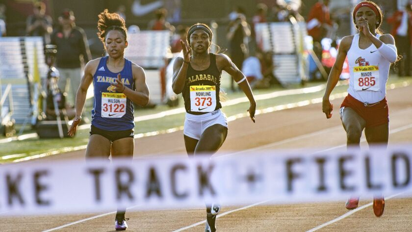 De'Anna Nowling of Calabasas, center, competes in the Women's 100 Meter Dash Invitational during the