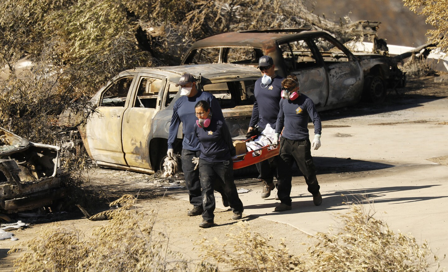 Los Angeles County coroner's workers recover a body at a burned home in the 32000 block of Lobo Canyon Road in Agoura Hills on Wednesday.