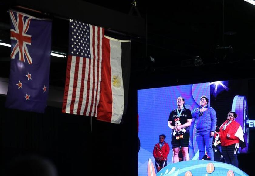 Sarah Elizabeth Robles de EE.UU. (c), Laurel Hubbard de Nueva Zelanda (i) y Shaimaa Ahmed Khalaf Haridy de Egipto (d) posan en el podio durante el himno nacional estadounidense en la premiación de la competencia femenina arriba de 90 kilos en el Campeonato Mundial de Halterofilia en el Anaheim Convention Center. EFE
