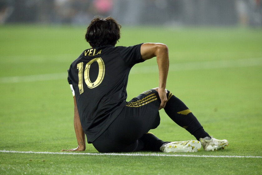 LAFC forward Carlos Vela holds his hamstring shortly after scoring a second half goal against the Galaxy.
