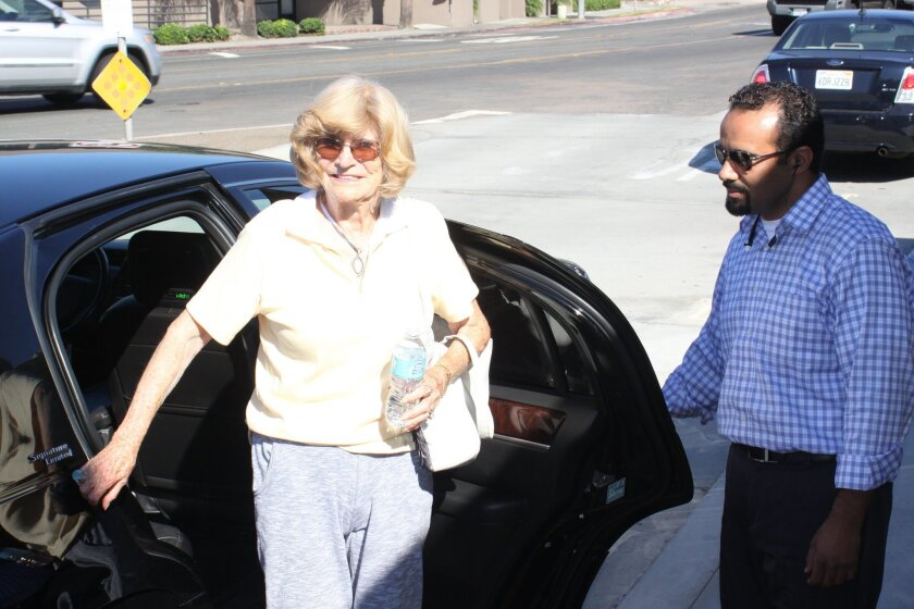 Marjorie Berns of La Jolla takes the Senior Express to the Community Center with assistance from driver Youness Hansel for an iPhone class.