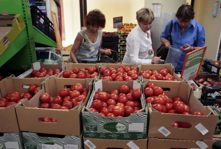 Women choose Dutch tomatoes at a supermarket in downtown Moscow, on Thursday, Aug. 7, 2014. The Russian government has banned all imports of meat, fish, milk and milk products and fruit and vegetables from the United States, the European Union, Australia, Canada and Norway, Prime Minister Dmitry Medvedev announced Thursday. The move was taken on orders from President Vladimir Putin in response to sanctions imposed on Russia by the West over the crisis in Ukraine. The ban has been introduced for one year. (AP Photo/Ivan Sekretarev)