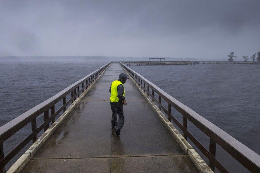 Storm chaser Shaun Piegdon walks down a pier over Louisiana's Lake Arthur on Friday.