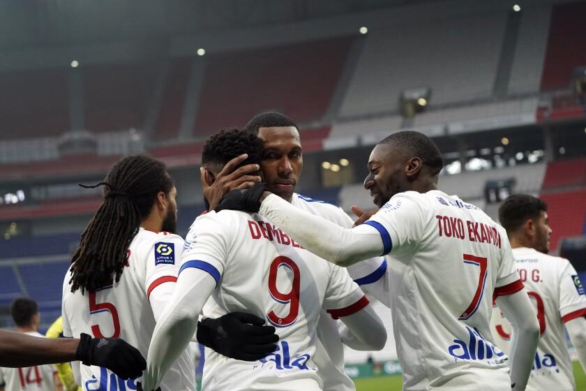 Moussa Dembele (centro) celebra tras anotar un gol para Lyon en el partido contra Reims en la liga francesa, el domingo 29 de noviembre de 2020. (AP Foto/Laurent Cipriani)