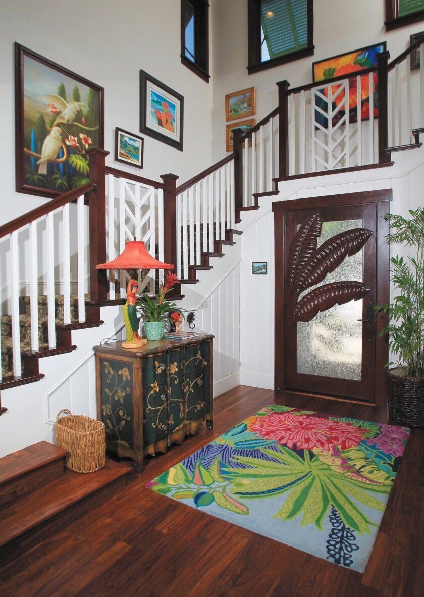 Custom-carved entry doors and paintings above the staircase add to the tropical vibe in the home.