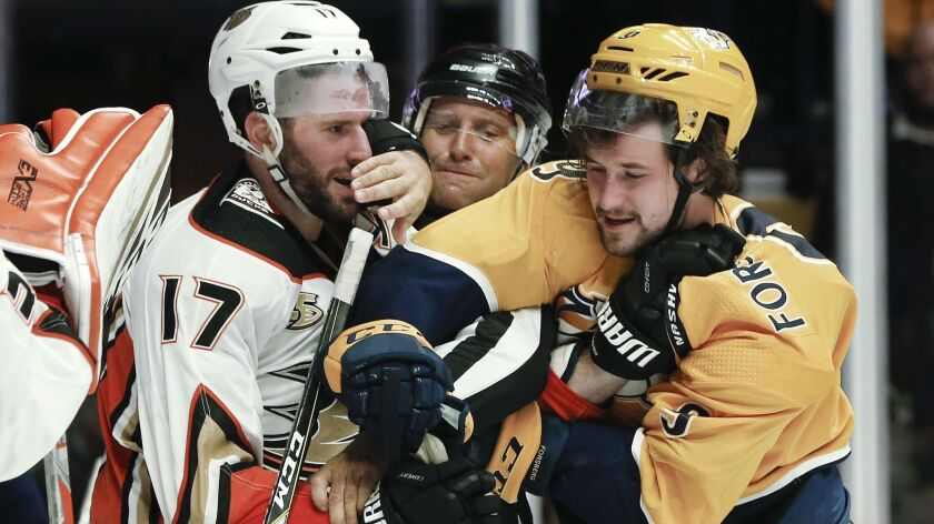 Ducks center Ryan Kesler (17) and Nashville Predators left wing Filip Forsberg (9) fight as linesman Jonny Murray, center, tries to pull them apart during the second period on Sunday.
