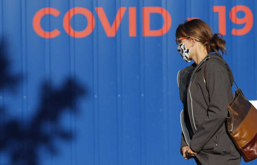 A woman wearing a face mask walks to get tested for COVID-19 at a sampling station in Prague, Czech Republic, Friday, Sept. 18, 2020. The Czech Republic has been been facing the second wave of infections. The number of new confirmed coronavirus infections has been setting new records almost on a daily basis, currently surpassing 3,000 cases in one day for the first time. (AP Photo/Petr David Josek)