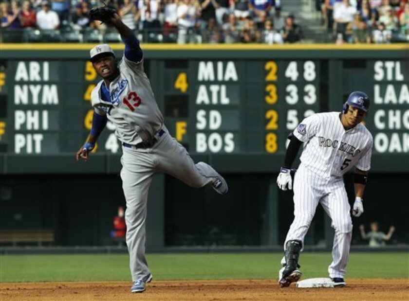 Los Angeles Dodgers shortstop Hanley Ramirez, left, jumps to field a throw from the outfield as Colorado Rockies' Carlos Gonzalez, right, pulls into second base with an RBI-double in the first inning of a baseball game in Denver, Thursday, July 4, 2013. (AP Photo/David Zalubowski)