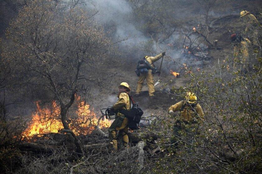 Firefighters battle a 150-acre brush fire south of Highway 138 near Gorman.
