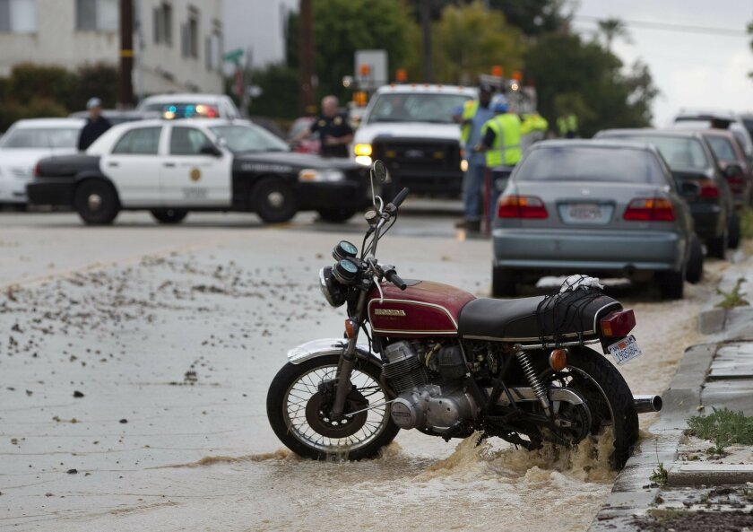 Along Florida Street water rushes down the street swamping cars and this motorcycle.