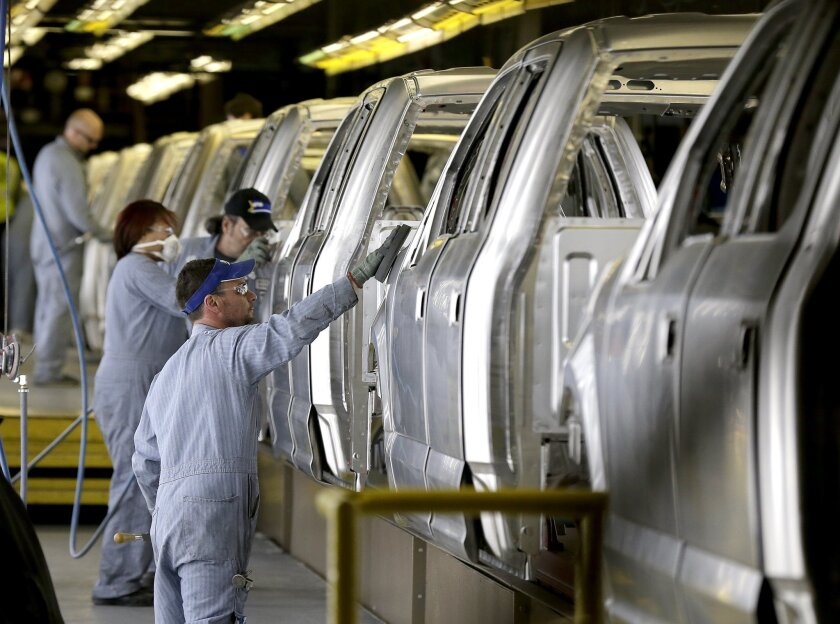 Workers inspect Ford F-150 trucks before they get painted at the company's Kansas City Assembly Plant in Claycomo, Mo.