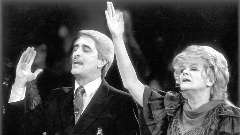 Paul and Jan Crouch raise their hands in praise during a song at a revival meeting at the Cathedral of Light in Selma, Calif., on Aug. 18, 1988.
