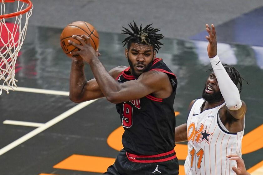 Chicago Bulls forward Patrick Williams (9) grabs a rebound away from Orlando Magic forward James Ennis III (11) during the second half of an NBA basketball game Friday, Feb. 5, 2021, in Orlando, Fla. (AP Photo/John Raoux)