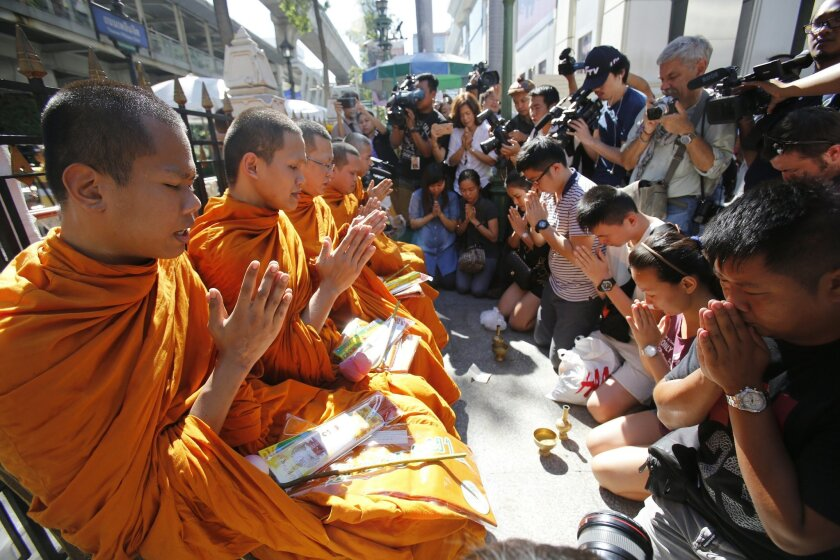 Buddhist monks hold a prayer at the Erawan Shrine at Rajprasong intersection in Bangkok, Thailand, Wednesday, Aug. 19, 2015. The central Bangkok shrine reopened Wednesday to the public after Monday's bomb blast as authorities searched for a man seen in a grainy security video who they say was the prime suspect in an attack authorities called the worst in the country's history. (AP Photo/Sakchai Lalit)