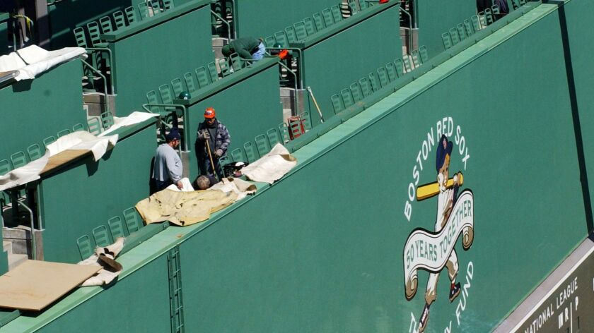"""Construction workers put together the finishing touches on the new seating area atop the """"Green Monster"""" during Fenway Park's renovation in 2003."""