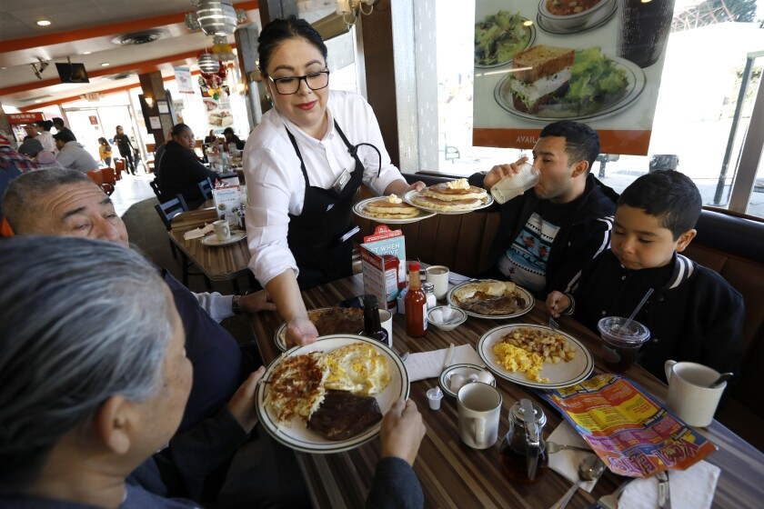 Waitress Maria Mundo serves a family at Norms in West Hollywood on a Monday morning.