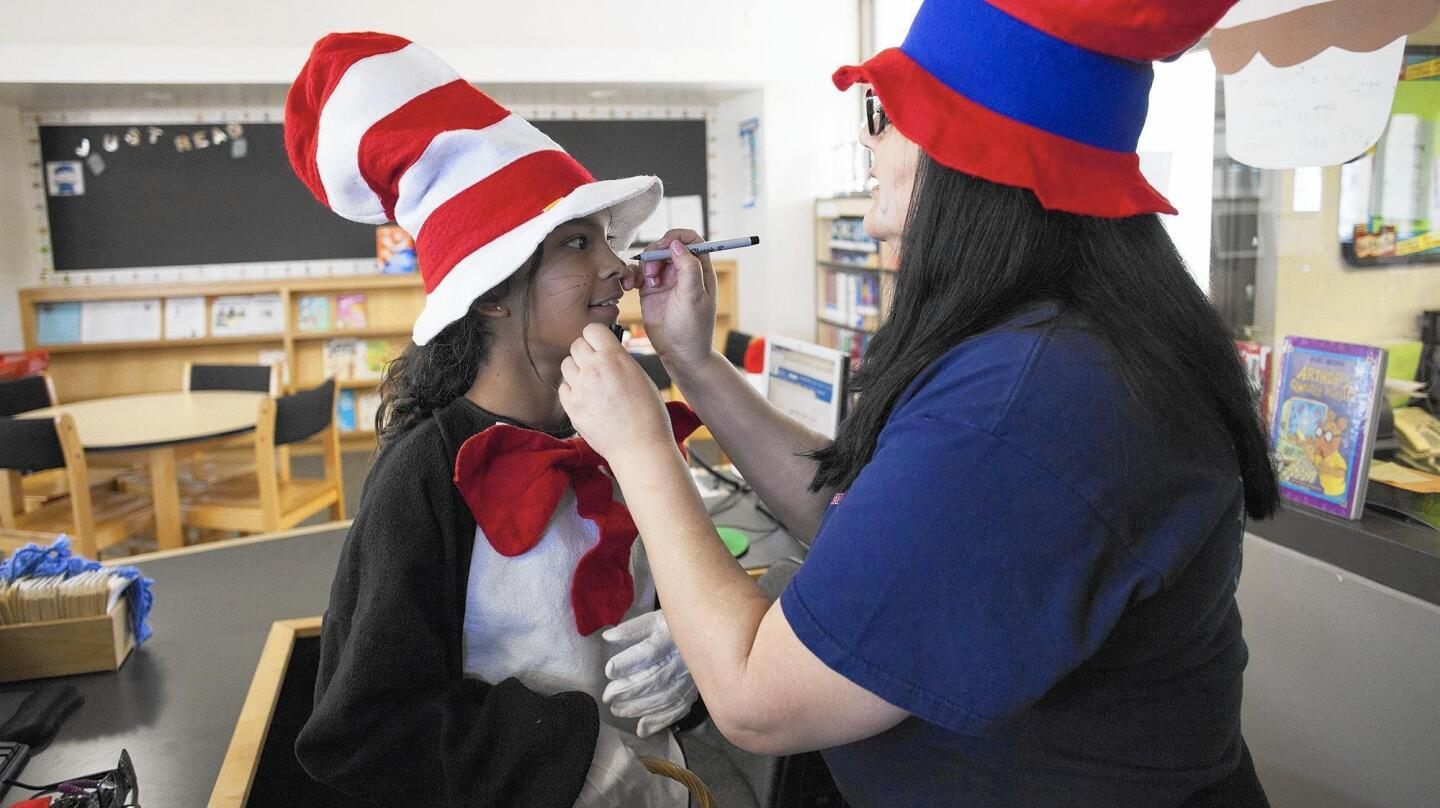 Sixth-grader Marisa Bist gets whiskers to go with her Cat in the Hat costume, courtesy of librarian Carmen McCormick on Thursday during Newport Coast Elementary School's celebration of Dr. Seuss' birthday.