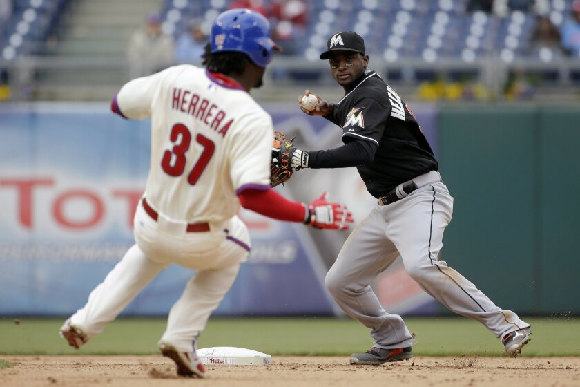 Miami Marlins shortstop Adeiny Hechavarria, right, looks to throw to first base after forcing out Philadelphia Phillies' Odubel Herrera at second on a double play by Ben Revere during the eighth inning of a baseball game, Thursday, April 23, 2015, in Philadelphia. Revere was out at first. Miami won 9-1. (AP Photo/Matt Slocum)