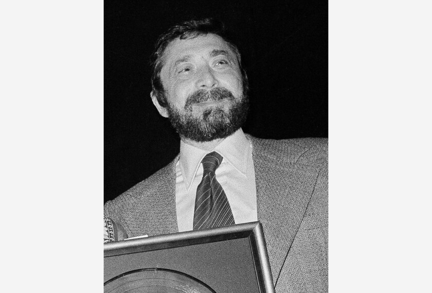 """FILE - Walter Yetnikoff, president of CBS Records, presents gold records in New York on Jan. 17, 1978. Yetnikoff, the rampaging, R-rated head of CBS Records who presided over blockbuster releases by Michael Jackson, Billy Joel and many others and otherwise devoted his life to a self-catered feast of """"schmoozing, shmingling and bingling,"""" has died at age 87. Yetnikoff's death was confirmed Tuesday, Aug. 10, 2021, by David Ritz, who collaborated with Yetnikoff on his memoir """"Howling at the Moon."""" (AP Photo/Carlos Rene Perez, File)"""