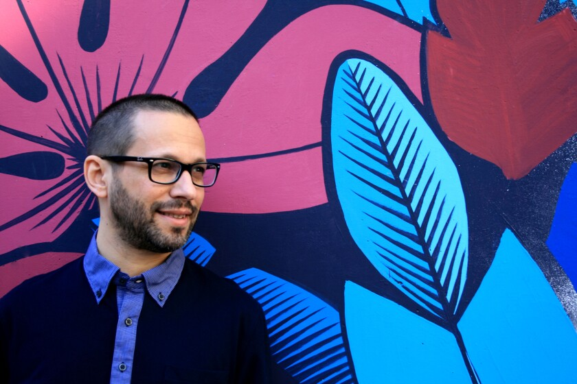 Lawrence Schimel in front of a bold mural of leaves