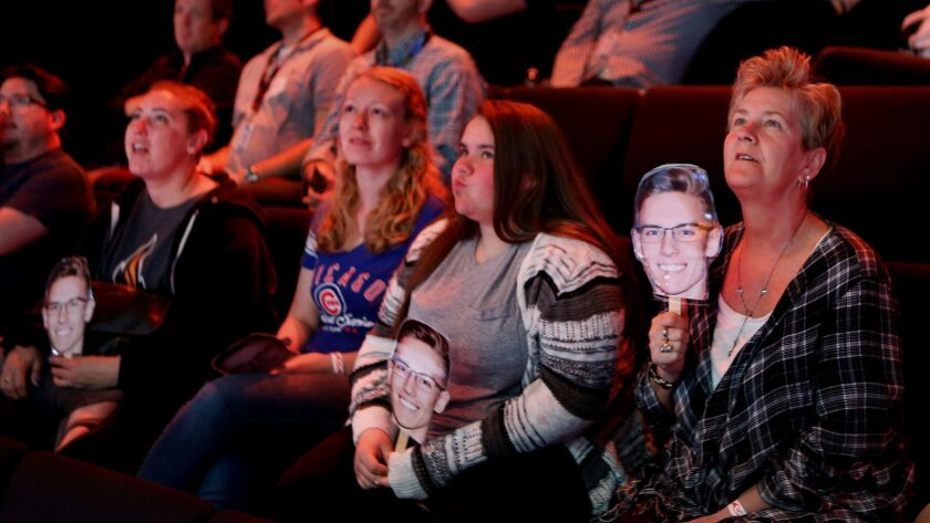 "Janice Davern, right, along with other family members, all holding photographs of her grandson, T.J. Bjorklund, a member of the ""League of Legends"" team from the University of Illinois, watch a championship match against the University of Maryland."