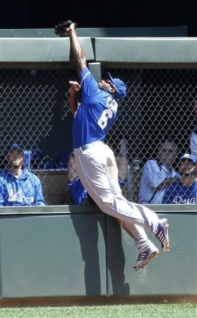 Kansas City Royals center fielder Lorenzo Cain jumps to make the catch on a ball hit by Minnesota Twins' Trevor Plouffe in the fifth inning of a baseball game in Minneapolis on Thursday, Aug. 1, 2013. The Royals won 7-2. (AP Photo/Andy Clayton-King)