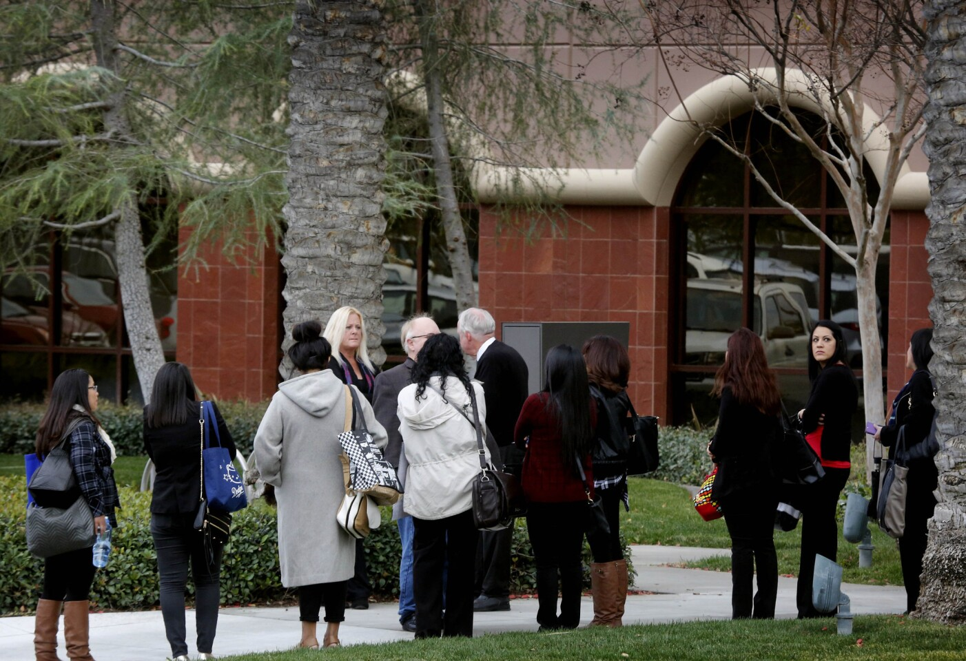 Employees wait to enter the Inland Regional Center complex in San Bernardino as it reopens for the first time since a mass shooting there last month that left 14 people dead.