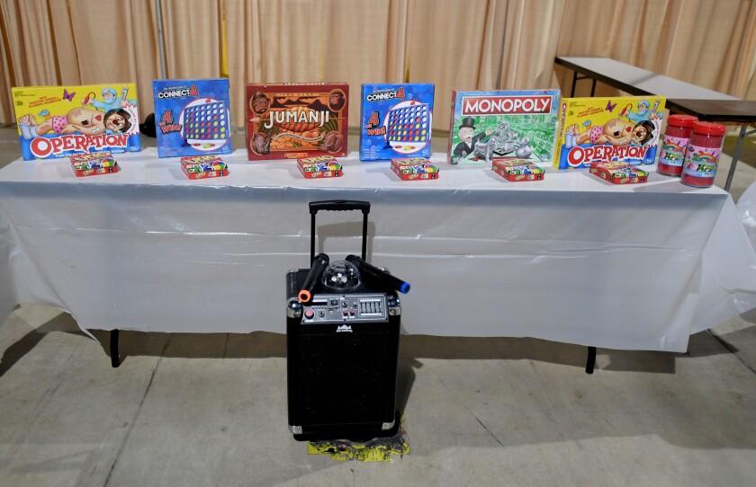 Board games sit on a table near a karaoke machine