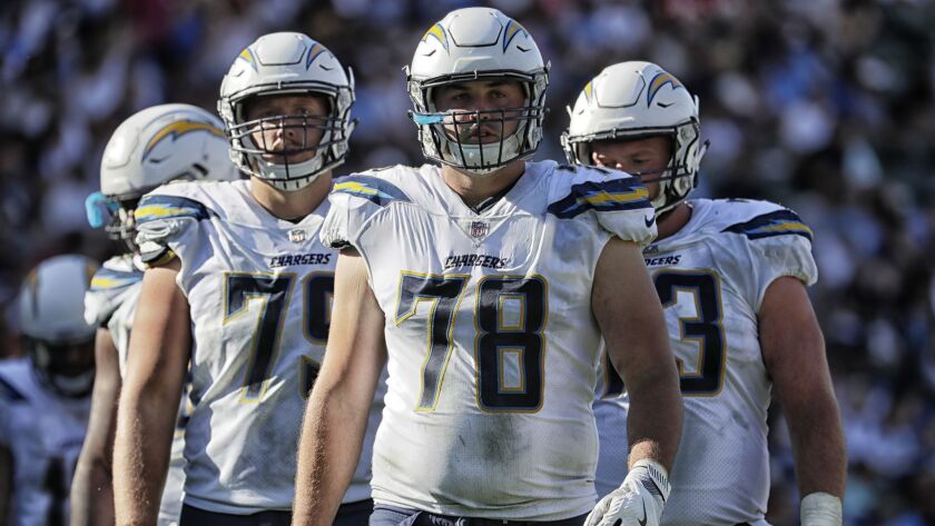 Chargers offensive linemen Kenny Wiggins, left, Michael Schofield and Spencer Pulley on the field during action against the Chiefs at StubHub Center.