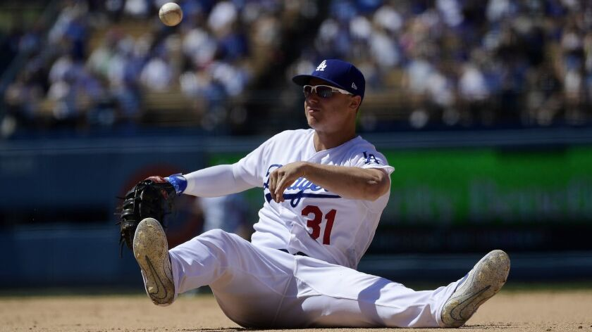 Dodgers' Joc Pederson throws out Colorado's Raimel Tapia at first during the seventh inning Sunday at Dodger Stadium.