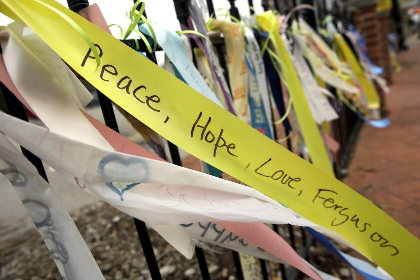 In this Dec. 9, 2014, photo, brightly colored ribbons flutter from a wrought-iron fence along the a main thoroughfare in Ferguson, Mo. Up and down South Florissant Road, paint has transformed the sheets of plywood covering windows broken during last month's rioting into works of art.  (AP Photo/Jef