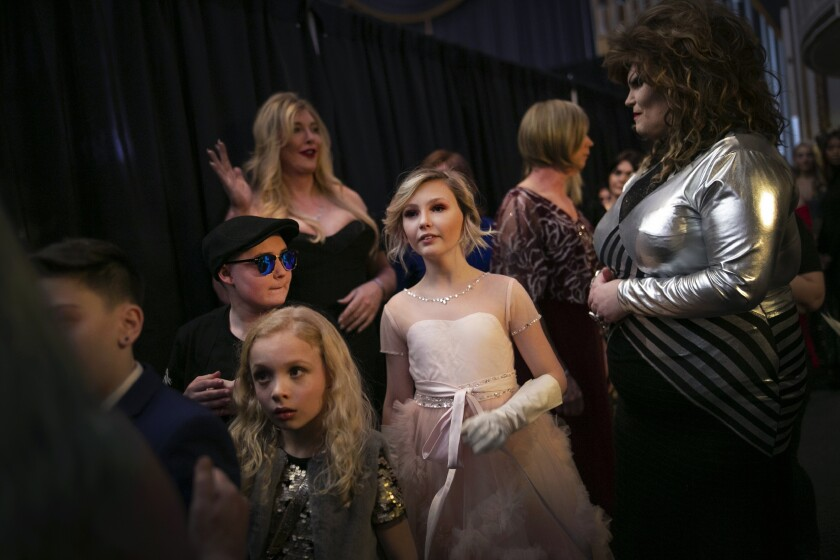 """Asher, 12, center, waits backstage to walk down the runway with others during a fashion show held by the Trans Club of New England on Friday, Jan. 31, 2020, in Boston. Asher identifies as non-binary and the preferred pronoun is just """"Asher."""" Teachers, staff and students in Asher's school have come to understand: Asher is not a boy, not a girl. Asher is non-binary. Asher is Asher. (AP Photo/Wong Maye-E)"""