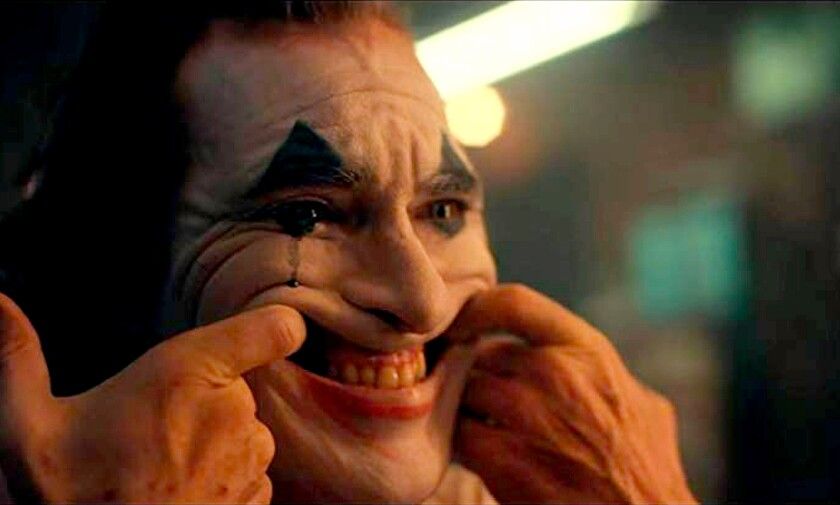 "Joaquin Phoenix, with his index fingers hooked in his mouth, pulls his face into an exaggerated grin as the title character in ""Joker."""