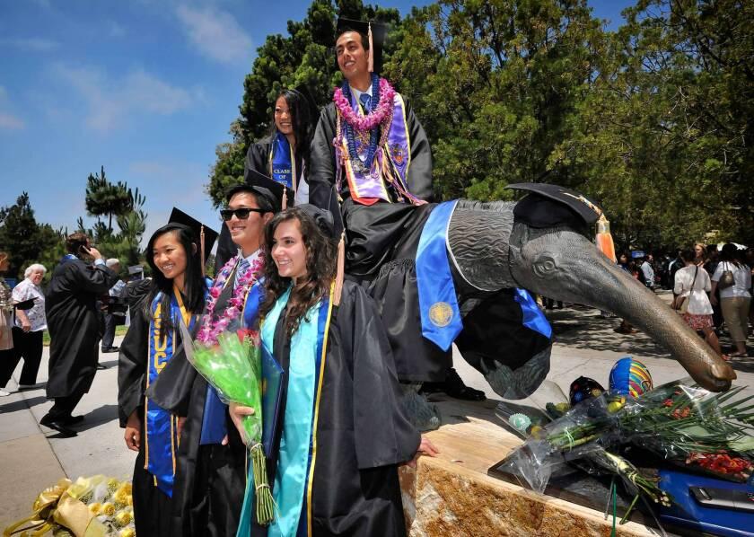 UC Irvine graduates gather around the school's Anteater mascot on June 18, 2012.