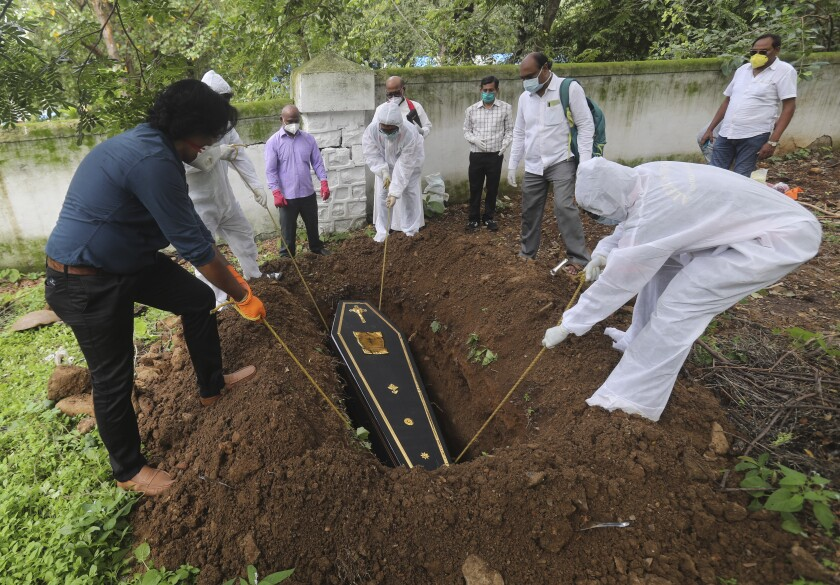 People lower the coffin of a man who died of COVID-19 at a cemetery in India.