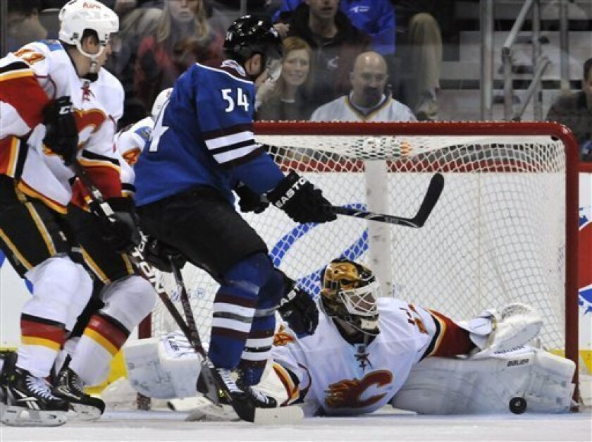 Calgary Flames goalie Miikka Kiprusoff, of Finland, blocks a shot by Colorado Avalanche right wing David Jones (54) as Flames center Mikael Backlund (11), of Sweden, moves in during the second period in an NHL hockey game in Denver on Sunday, April 3, 2011. (AP Photo/Joe Mahoney)