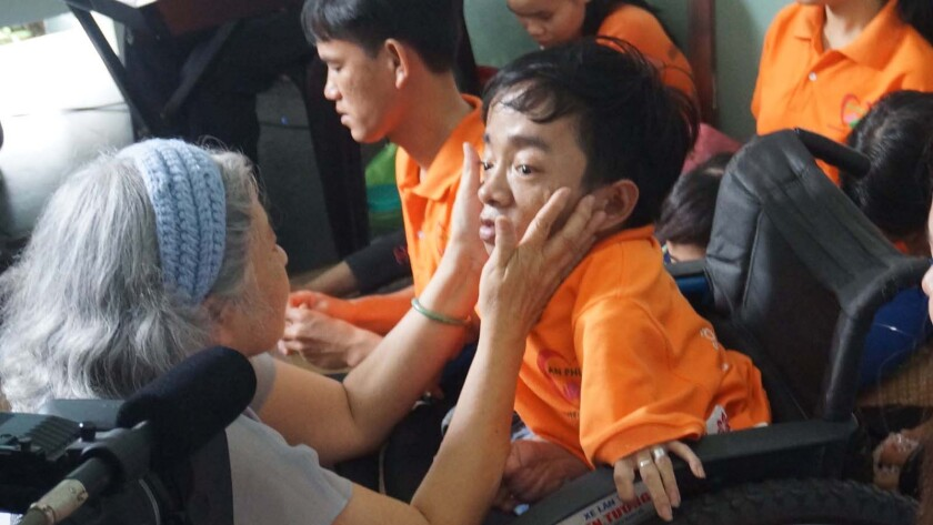 Activist Tran To Nga touches a boy's face