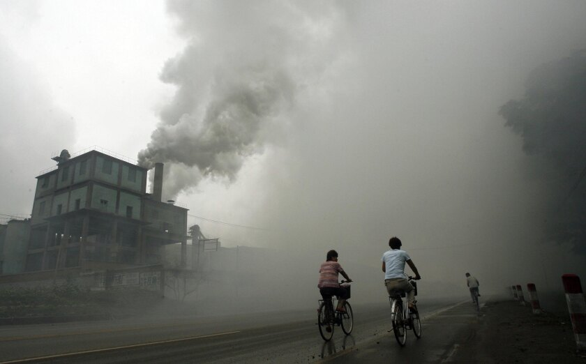 Cyclists passing through thick pollution from a factory in Yutian, 100km east of Beijing in China's northwest Hebei province in 2006.