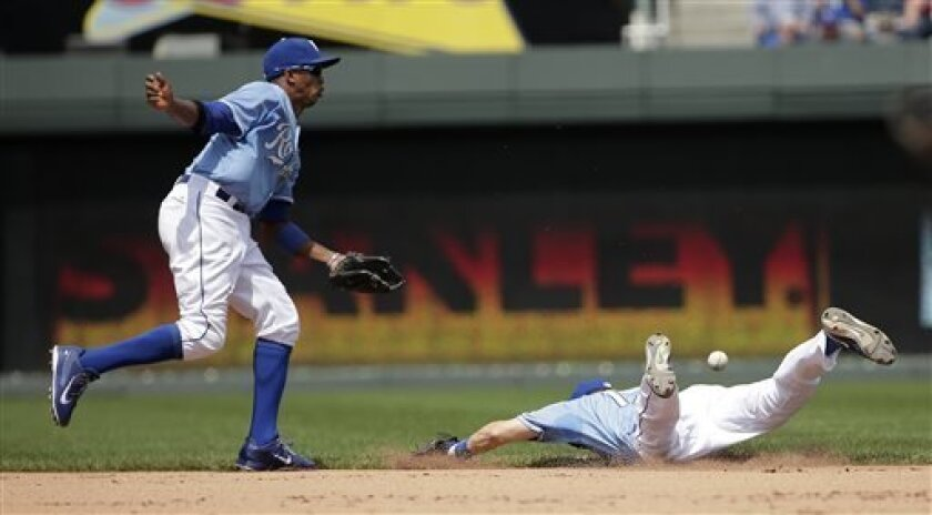 An RBI single hit by Miami Marlins' Justin Ruggiano gets past Kansas City Royals shortstop Alcides Escobar, left, and second baseman Chris Getz during the fourth inning of a baseball game Wednesday, Aug 14, 2013, in Kansas City, Mo. (AP Photo/Charlie Riedel)