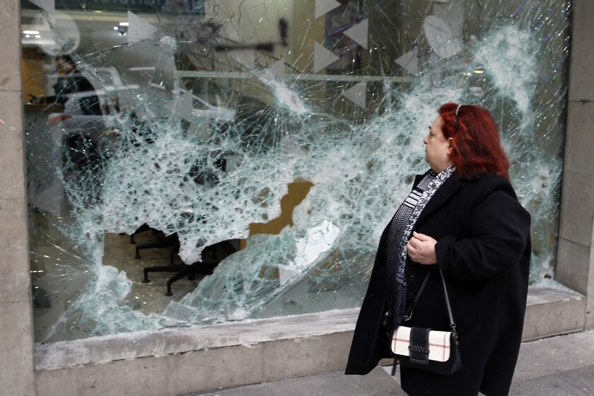 A woman looks at the broken glass of Bank of Beirut that was smashed by anti-government protesters in Beirut, Lebanon, Wednesday, Jan. 15, 2020. Banks in Hamra trade street were badly damaged after a night that witnessed clashes between anti-government protesters and Lebanese riot police. (AP Photo/Bilal Hussein)