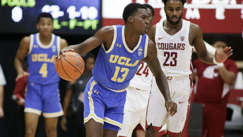 UCLA guard Kris Wilkes (13) dribbles the ball while defended by Washington State guard Ahmed Ali (23